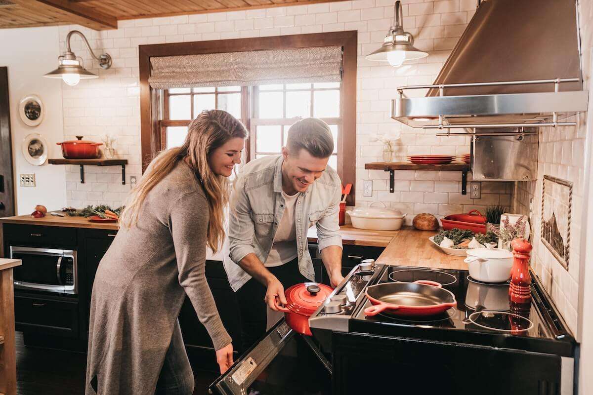 Young Couple Putting Food In The Oven In A Hot Kitchen With A Stainless Steel Range Hood